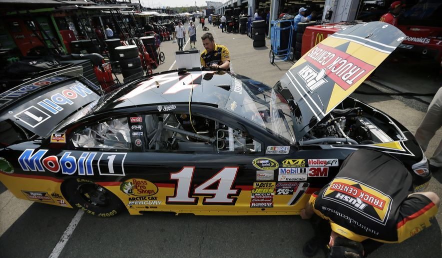 Tony Stewart's crew works on his race car in the garage area before a practice session for Sunday's NASCAR Sprint Cup Series auto race at Watkins Glen International, Friday, Aug. 8, 2014, in Watkins Glen N.Y. (AP Photo/Mel Evans)