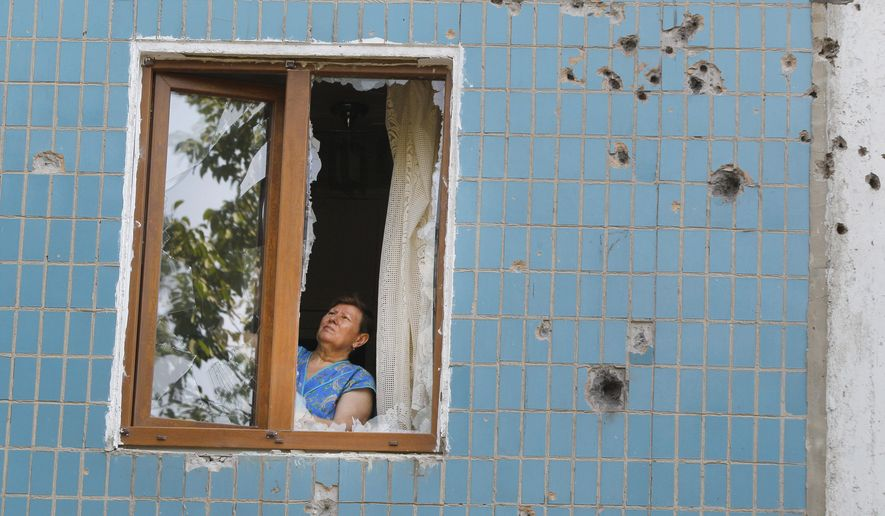 A local woman works on her window after shelling in Donetsk, eastern Ukraine, Friday, Aug. 8, 2014. At least three civilians have been killed and another 10 wounded in overnight shelling of the main rebel stronghold in eastern Ukraine besieged by government forces, officials said. (AP Photo/Sergei Grits)