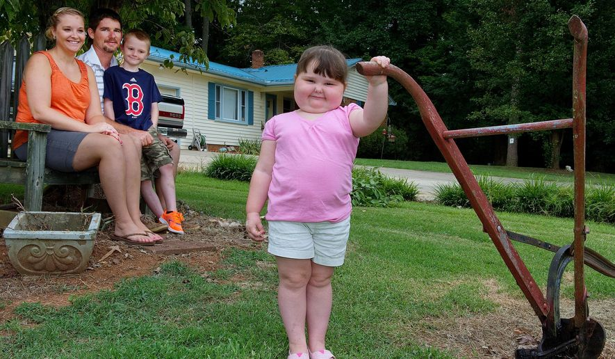 FOR RELEASE MONDAY, AUGUST 11, 2014, AT 12:01 A.M. EDT - In this July 31, 2014 photo, Rylee Lambeth, 4, stands in her great-grandparents' front yard with her family, from left, parents Jessica and Robert, and her brother, 8-year-old Bryson, near Lexington, N.C. Rylee has a rare autoimmune disease that severely affected her motor skills, and subsequent treatments have caused her to swell excessively, especially her face. (AP Photo/The Lexington Dispatch, Donnie Roberts)
