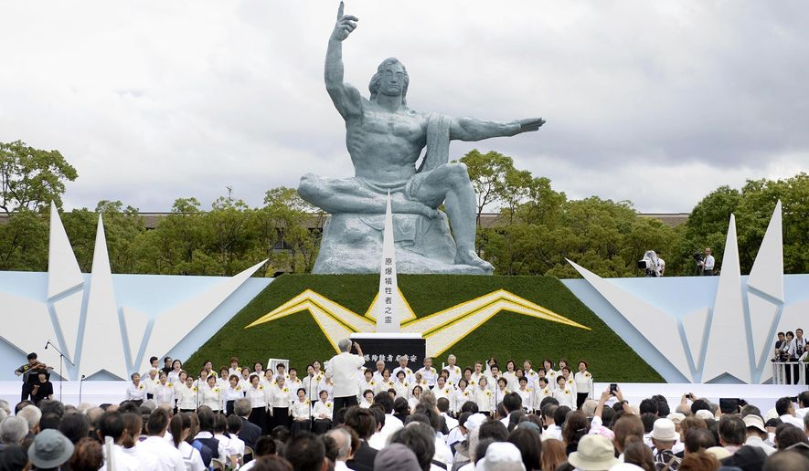 People listen to chorus during a ceremony in front of the Statue of Peace at Nagasaki Peace Park to mark the 69th anniversary of the world's second atomic bomb attack, in Nagasaki, southern Japan Saturday, Aug. 9, 2014. (AP Photo/Kyodo News) JAPAN OUT, MANDATORY CREDIT