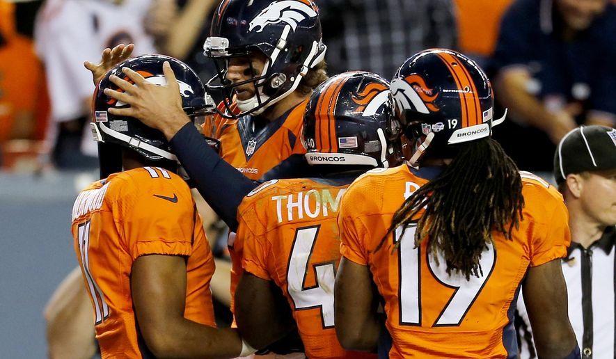 Denver Broncos quarterback Brock Osweiler, rear, celebrates with Jordan Norwood (11) after Norwood scored a touchdown against the Seattle Seahawks during the second half of an NFL preseason football game, Thursday, Aug. 7, 2014, in Denver. (AP Photo/Joe Mahoney)