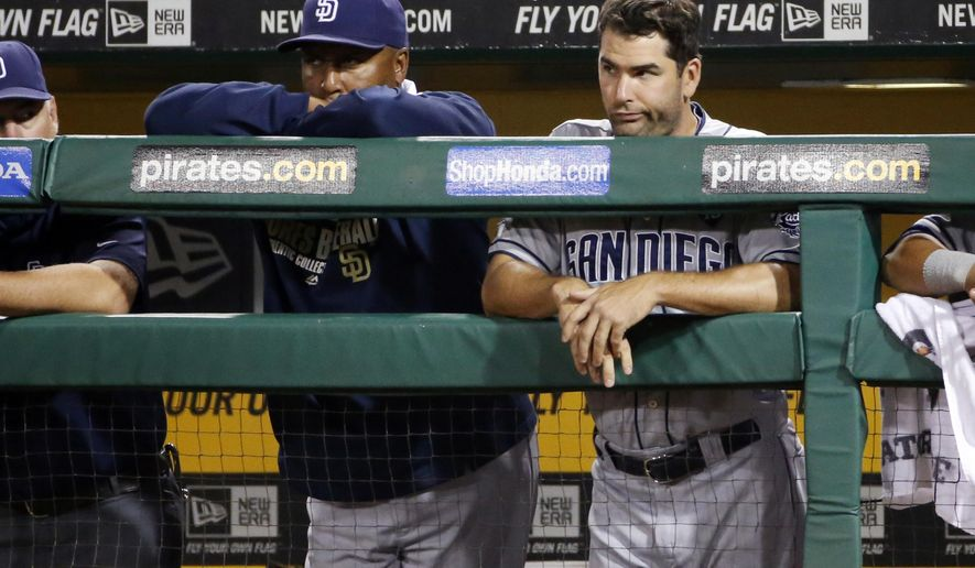 San Diego Padres' Seth Smith, right, stands in the dugout during the ninth inning of a baseball game against the Pittsburgh Pirates in Pittsburgh, Friday, Aug. 8, 2014. The Pirates won 2-1. (AP Photo/Gene J. Puskar)