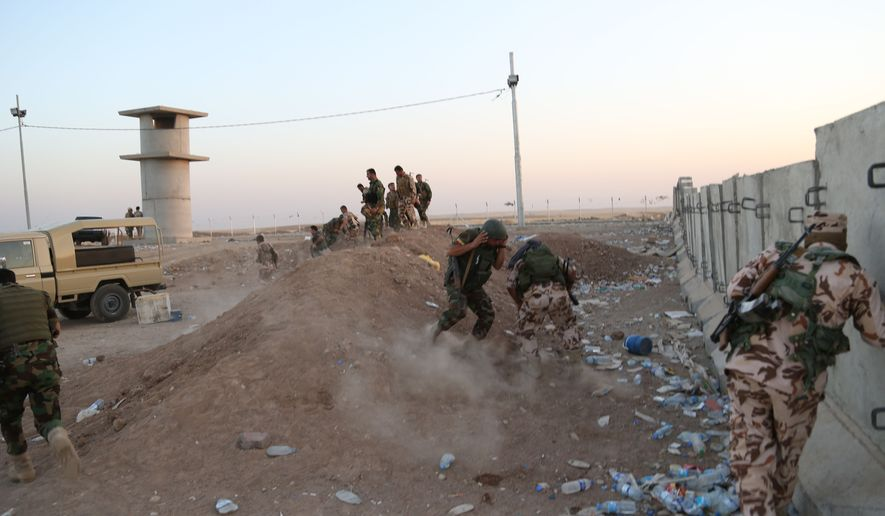 Kurdish Peshmerga fighters take cover during airstrikes targeting Islamic State militants near the Khazer checkpoint outside of the city of Irbil in northern Iraq, Friday, Aug. 8, 2014. Iraqi Air Force has been carrying out strikes against the militants, and for the first time on Friday, U.S. war planes have directly targeted the extremist Islamic State group, which controls large areas of Syria and Iraq. (AP Photo/Khalid Mohammed)