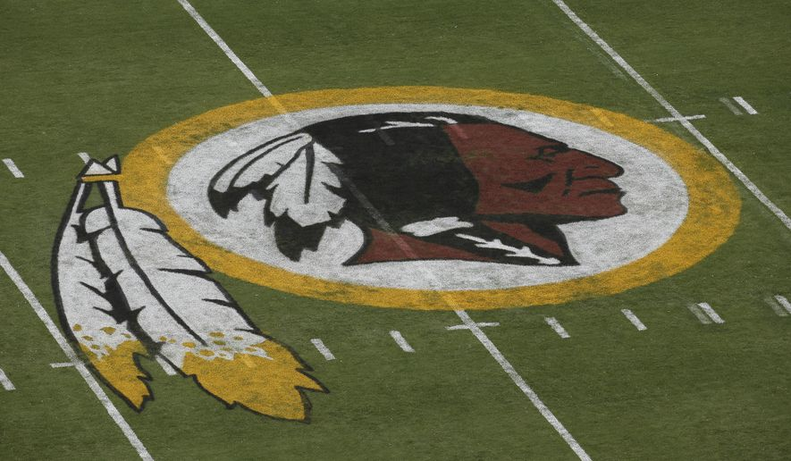 The Washington Redskins logo is seen on the field before an NFL football preseason game against the New England Patriots in Landover, Md., Thursday, Aug. 7, 2014. (AP Photo/Alex Brandon)