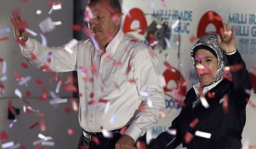 Turkish Prime Minister Recep Tayyip Erdogan and his wife Emine Erdogan wave to supporters after a rally in Ankara, Turkey, Friday, Aug. 8, 2014. Some 53 million Turks go the polls on Sunday to choose their 12th president in an election considered a turning point for the country of 76 million people, with Prime Minister Recep Tayyip Erdogan vying for the position he has pledged to transform from a symbolic role into a position of power. Ekmeleddin Ihsanoglu, the former chief of the Organization of Islamic Cooperation, and Kurdish politician Selahattin Demirtas are also running. (AP Photo/Burhan Ozbilici)