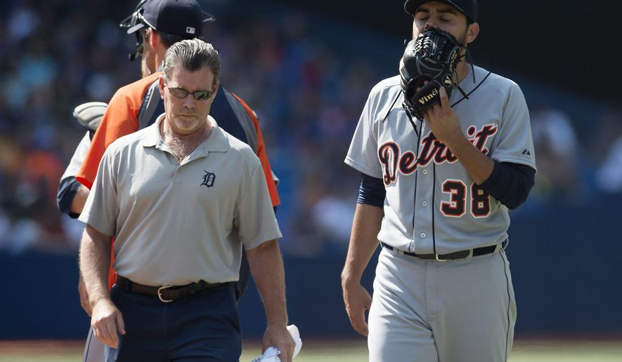 Detroit Tigers relief pitcher Joakim Soria, right, walks off the field with a team trainer in the tenth inning of a baseball game against the Toronto Blue jays, Saturday, Aug. 9, 2014 in Toronto. The Blue Jays defeated the Tigers 3-2. (AP Photo/The Canadian Press, Darren Calabrese)