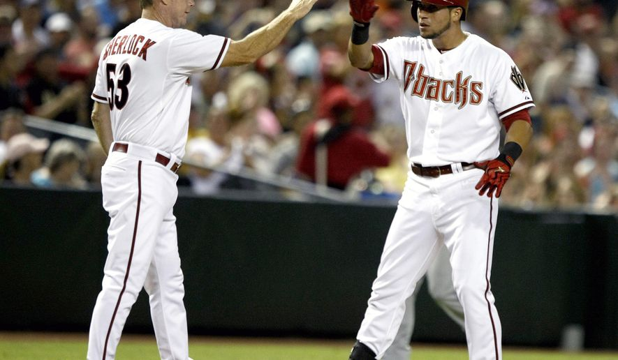 Arizona Diamondbacks' David Peralta (6) celebrates with third base coach Glenn Sherlock (53) after hitting a seventh-inning RBI triple against the Colorado Rockies during a baseball game, Friday, Aug. 8, 2014, in Phoenix. (AP Photo/Rick Scuteri)