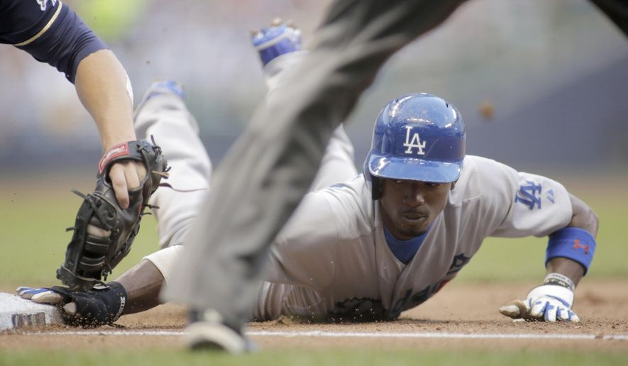 Los Angeles Dodgers' Dee Gordon, right, is called safe at first base against the Milwaukee Brewers during the sixth inning of a baseball game Saturday, Aug. 9, 2014, in Milwaukee. (AP Photo/Darren Hauck)
