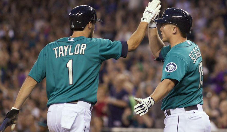 Seattle Mariners' Kyle Seager, right, congratulates Chris Taylor after Taylor scored during the fifth inning of a baseball game against the Chicago White Sox, Friday, Aug. 8, 2014, in Seattle. (AP Photo/Stephen Brashear)