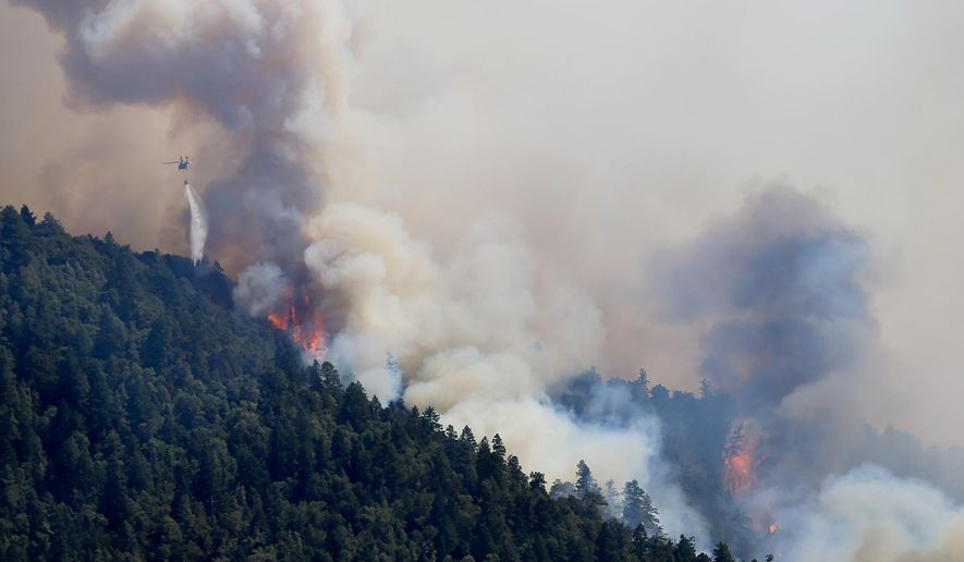 An Air National Guard helicopter makes a water drop as the Lodge Fire between Legget tand Laytonville, Calif., jumps the Eel River and moves upslope, Friday Aug. 8, 2014.  The fire was started by lightning on July 30 and has grown to 5,400 acres.   (AP PhotoThe Press Democrat, Kent Porter)