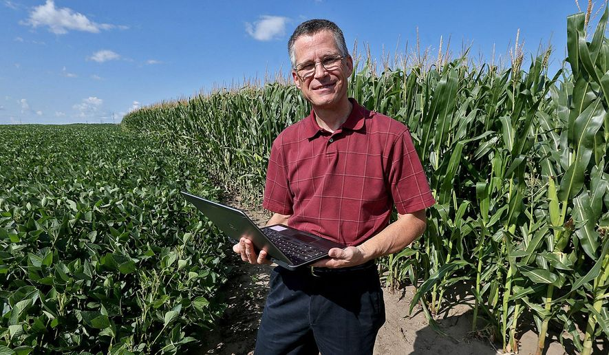 ADVANCE FOR RELEASE SATURDAY, AUG. 9, 2014, AT 12:01 A.M. CDT. AND THEREAFTER- In this July 29, 2014 photo, Stan Buman, conservation specialist with United Suppliers of Ames, holds his laptop as stands in a field of soybeans, left, and corn in Johnston, Iowa. Buman will work with Iowa farmers to provide conservation planning services through their local elevators. (AP Photo/The Des Moines Register, Bill Neibergall)  MAGS OUT, TV OUT, NO SALES, MANDATORY CREDIT