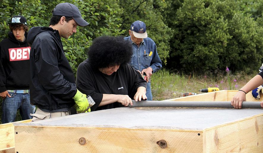 This Aug. 2, 2014, photo shows volunteers lining up raised beds in road at the community garden in Kodiak, Alaska. (AP Photo/Kodiak Daily Mirror, Julie Hermann)