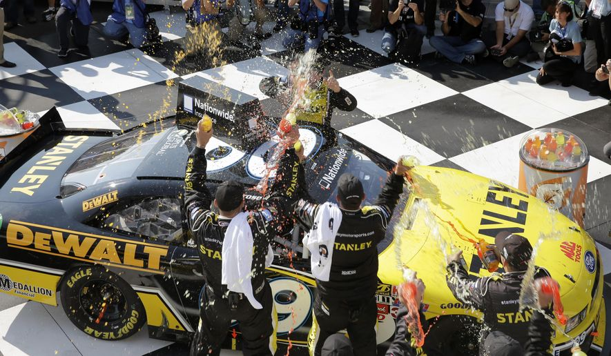 Marcos Ambrose is doused by his race team as he climbs from his car to celebrate in Victory Lane after winning a NASCAR Nationwide Series auto race at Watkins Glen International, Saturday, Aug. 9, 2014, in Watkins Glen N.Y. (AP Photo/Mel Evans)