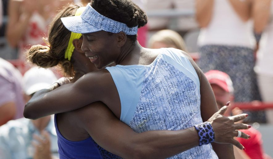 Venus Williams of the United States hugs her sister Serena after beating her 6-7, 6-2, 6-3 during semifinal play at the Rogers Cup tennis tournament Saturday, Aug. 9, 2014, in Montreal. (AP Photo/The Canadian Press, Paul Chiasson)