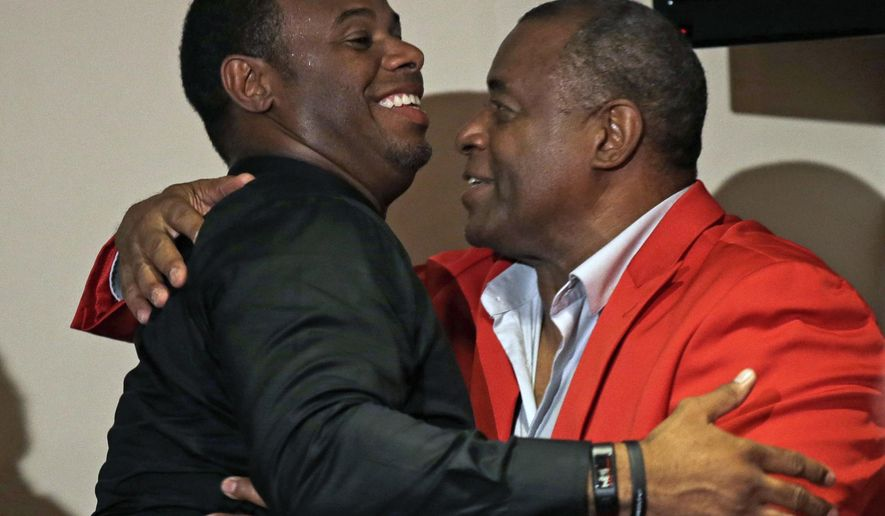 Ken Griffey Jr., left, hugs his father, Ken Griffey, at the start of news conference, Saturday, Aug. 9, 2014, in Cincinnati. Griffey Jr. will be inducted into the Cincinnati Reds hall of fame in ceremonies before a baseball game between the Cincinnati Reds and the Miami Marlins Saturday. Griffey Jr. will be joining his father in the Reds hall of fame. (AP Photo/Al Behrman)