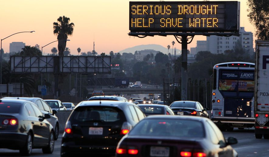 FILE - In this Feb. 14, 2014, file photo, morning traffic makes it's way toward downtown Los Angeles along the Hollywood Freeway past an electronic sign warning of severe drought. In Santa Cruz, Calif., dozens of residents who violated their strict water rations take a seat at Water School, hoping to get hundreds of thousands of dollars in distressing penalties waived. California is in the third year of the state's worst drought in recent history. (AP Photo/Richard Vogel, File)