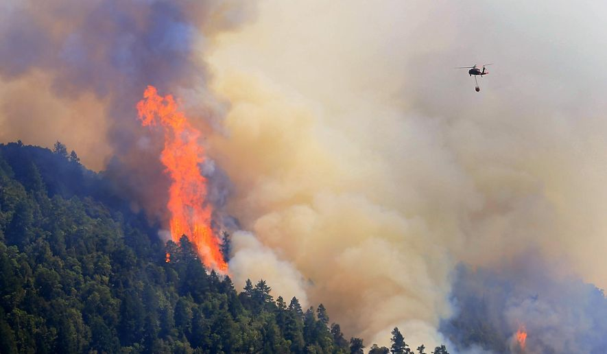 An Air National Guard helicopter moves in to make a water drop as the Lodge Fire Complex between Leggett and Laytonville, Calif., on  Friday Aug. 8, 2014.   Officials say eight firefighters who suffered burns while battling a wildfire in Northern California have been taken to the hospital. California Department of Forestry and Fire Protection Capt. Carlos Guerrero said Saturday that the injured firefighters are in stable condition after being airlifted to the burn center at the University of California, Davis for treatment. Officials say three firefighters from Santa Clara County and five inmate firefighters were burned fighting a blaze in Mendocino County late Friday night. (AP Photo, Kent Porter, Santa Rosa Press Democrat)