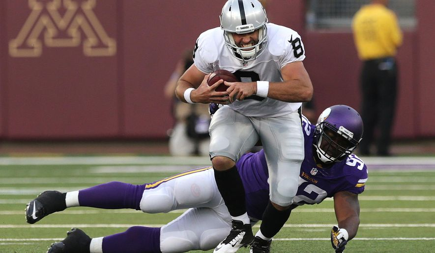 Minnesota Vikings defensive tackle Tom Johnson (92) sacks Oakland Raiders quarterback Matt Schaub (8) in the first half of a preseason NFL football game in Minneapolis, Friday, Aug. 8, 2014. (AP Photo/Jim Mone)