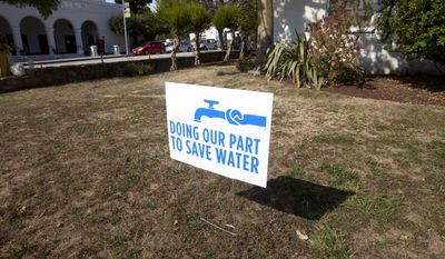 A water conservation sign is shown displayed outside of City Hall in Santa Cruz, Calif., Tuesday, July 29, 2014. Unlike most cities that have either groundwater, a connection to state water canals, or vast reservoirs, Santa Cruz is among those worst hit by the drought because it relies almost exclusively on storm runoff into a river, some creeks and an aging reservoir. (AP Photo/Bay Area News Group, Patrick Tehan)