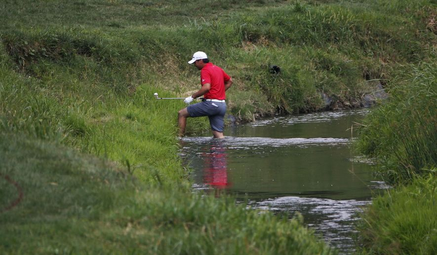 Jason Day, of Australia, crosses the water on the second hole during the third round of the PGA Championship golf tournament at Valhalla Golf Club on Saturday, Aug. 9, 2014, in Louisville, Ky. (AP Photo/Mike Groll)