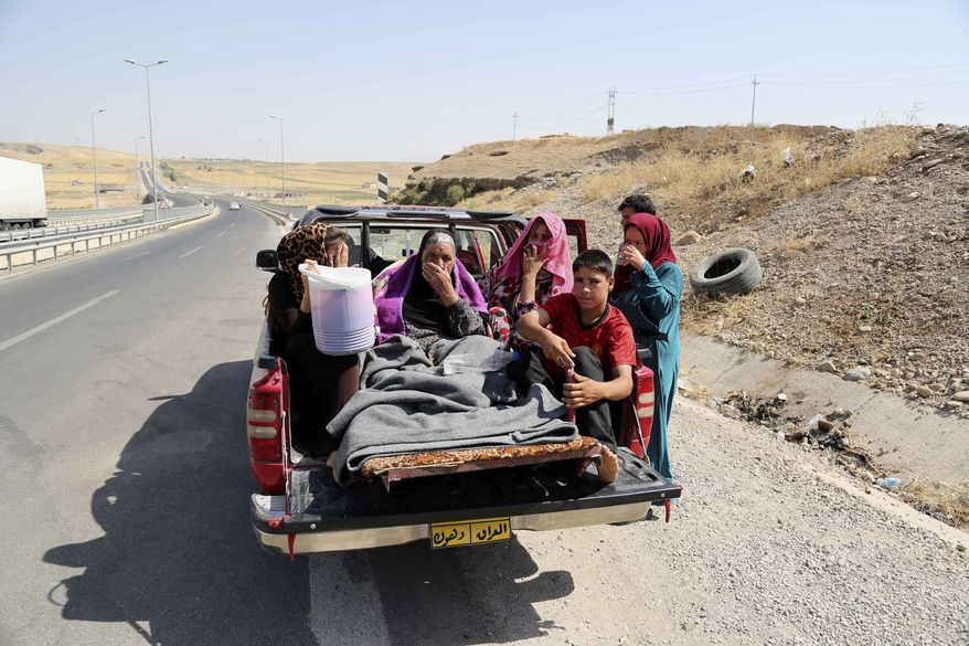 Displaced Iraqis ride on a truck on a mountain road near the Turkish-Iraq border, outside Dahuk, in Iraq on Saturday, Aug. 9, 2014. Islamic militants attacked the towns of Sinjar and Zunmar a few days ago. (AP Photo/ Khalid Mohammed)