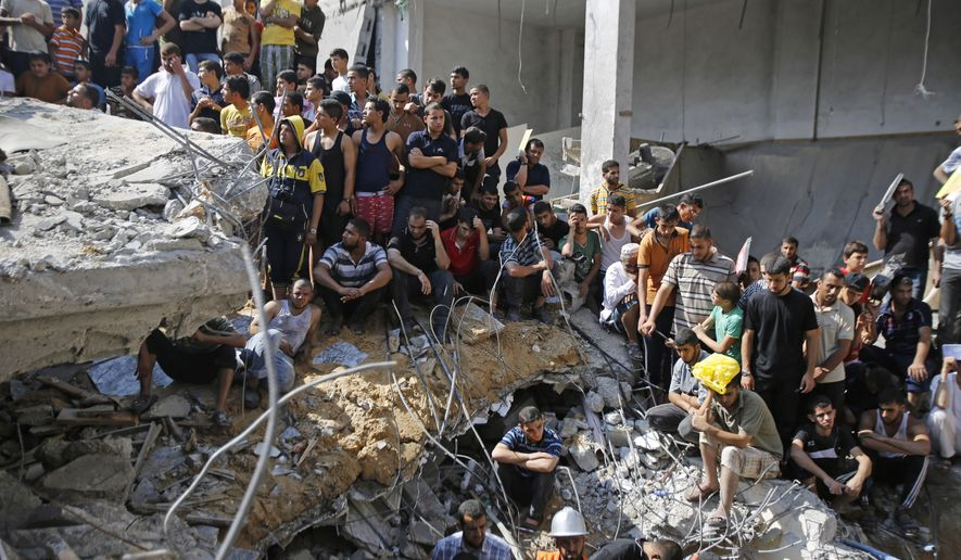 Palestinians gather on the rubble of al-Qassam mosque in Nuseirat refugee camp, central Gaza Strip, after it was hit by an Israeli airstrike, Saturday, Aug. 9, 2014. (AP Photo/Hatem Moussa)
