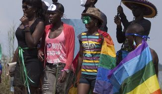 Ugandans take part in the 3rd Annual Lesbian, Gay, Bisexual and Transgender (LGBT) Pride celebrations in Entebbe, Uganda, Saturday, Aug. 9, 2014.  Scores of Ugandan homosexuals and their supporters are holding a gay pride parade on a beach in the lakeside town of Entebbe. The parade is their first public event since a Ugandan court invalidated an anti-gay law that was widely condemned by some Western governments and rights watchdogs. (AP Photo/Rebecca Vassie)
