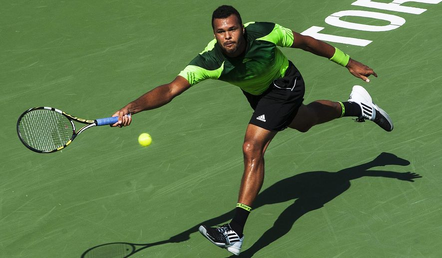 Jo-Wilfried Tsonga of France returns the ball against Roger Federer of Switzerland during the Rogers Cup Men's tennis tournament final in Toronto on Sunday, Aug. 10, 2014. (AP Photo/The Canadian Press, Aaron Vincent Elkaim)