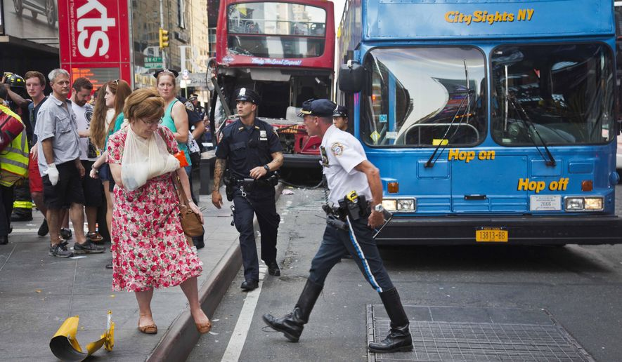 FILE- In this Aug. 5, 2014 file photo, woman, her arm bandaged and in a sling, leaves after being treated at the scene of a traffic accident apparently involving two double-decker tour buses in New York's Times Square. Although sightseeing buses are proliferating all over New York City, no single agency is charged with making sure their drivers and equipment are safe. (AP Photo/Bebeto Matthews, File)