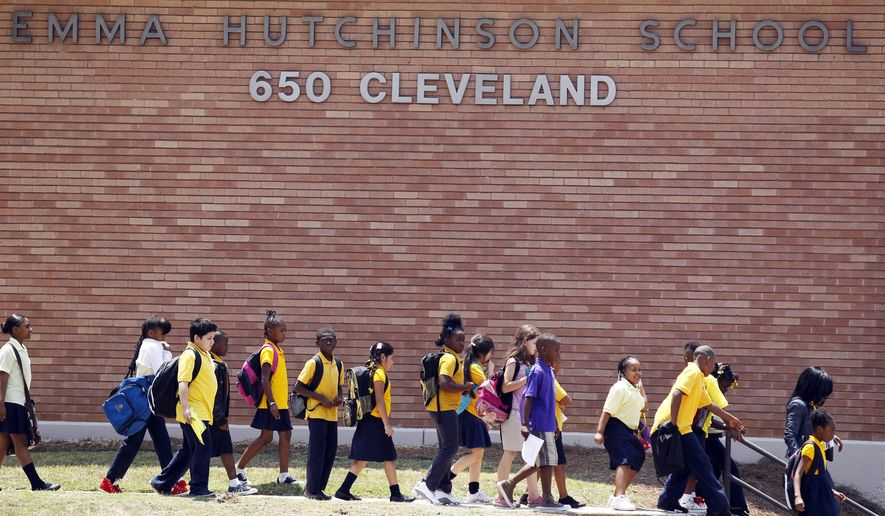 FILE - In a July 13, 2011 file photo, students at Emma Hutchinson School in Atlanta leave after the day's classes.  Hutchinson has been identified as one of forty four schools involved in a test cheating scandal.  Four years after questions first arose about testing scores in the Atlanta Public School district, the trial for 12 defendants is expected to begin on Aug. 11, 2014. Former superintendent Beverly Hall will not be among them after a judge ruled that breast cancer would prevent her from aiding in her defense.  (AP Photo/John Bazemore, File)