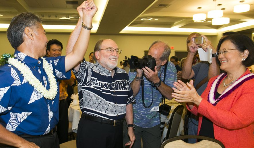 Hawaii Gov. elect David Ige, left, celebrates with Hawaii Gov. Neil Abercrombie, center, as US Sen. Maize Hirono, far right,  looks on during the Democratic Unity Breakfast, Sunday, Aug. 10, 2014 in Honolulu.  The breakfast is traditionally held after Hawaii elections and is attended by both winners as well as losers.  Fellow Democrat and State Sen. Ige defeated Abercrombie in a stunning primary-election defeat Saturday.  (AP Photo/Marco Garcia)