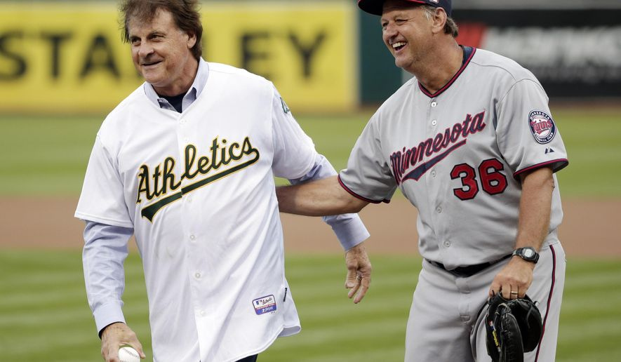 Former Oakland Athletics manager Tony La Russa, left, is hugged by Minnesota Twins bench coach Terry Steinbach during a ceremony celebrating La Russa's recent induction into the baseball Hall of Fame before a baseball game between the teams on Saturday, Aug. 9, 2014, in Oakland, Calif. (AP Photo/Marcio Jose Sanchez)