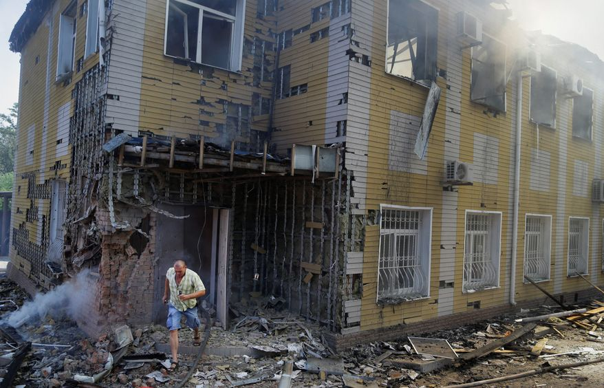 """A man runs out of the destroyed building after shelling in Donetsk, eastern Ukraine on Sunday. Fighting raged Sunday in the city despite a request from the pro-Russian rebels there for a cease-fire to prevent a """"humanitarian catastrophe."""" (Associated Press)"""