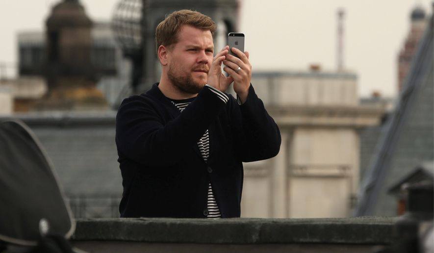 James Corden takes a panoramic photo on his camera phone on the rooftop of picturehouse cinemas in central London during a photo call for the film Begin Again, Wednesday, July 2, 2014. (Photo by Joel Ryan/Invision/AP)