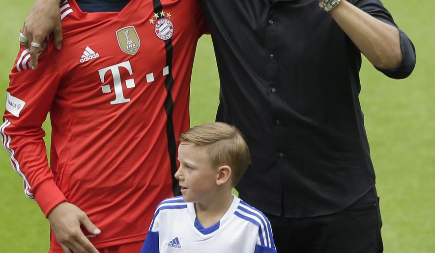 Singer Andreas Bourani, right, hugs Bayern Munich goalkeeper Manuel Neuer, as he performs during an official team presentation in the Allianz Arena stadium for the new German first division Bundesliga soccer season, in Munich, southern Germany, Saturday, Aug. 9, 2014. 65,000 spectators attended the event. (AP Photo/Matthias Schrader)