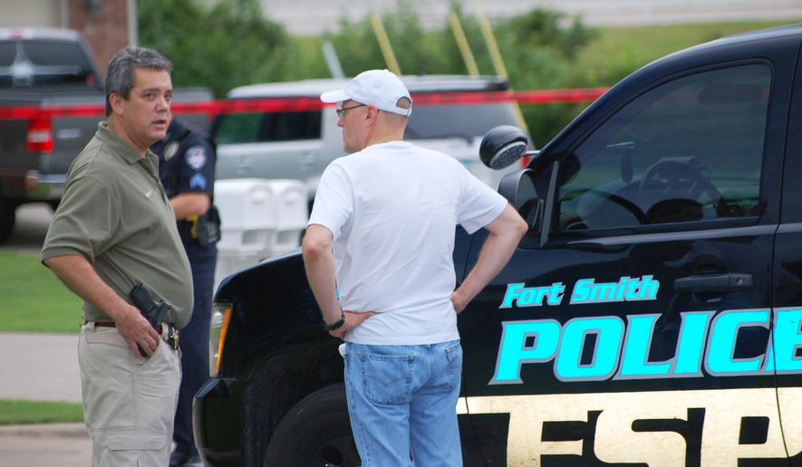 Sebastian County Sheriff Bill Hollenbeck, left, speaks with Sebastian County prosecuting attorney Dan Shue at the scene of a shooting Saturday, Aug. 9, 2014, outside a residence near Belhaven View Court and Brooken Hill Drive in Fort Smirth, Ark. (AP Photo/The Southwest Times Record, Stacy Ryburn)