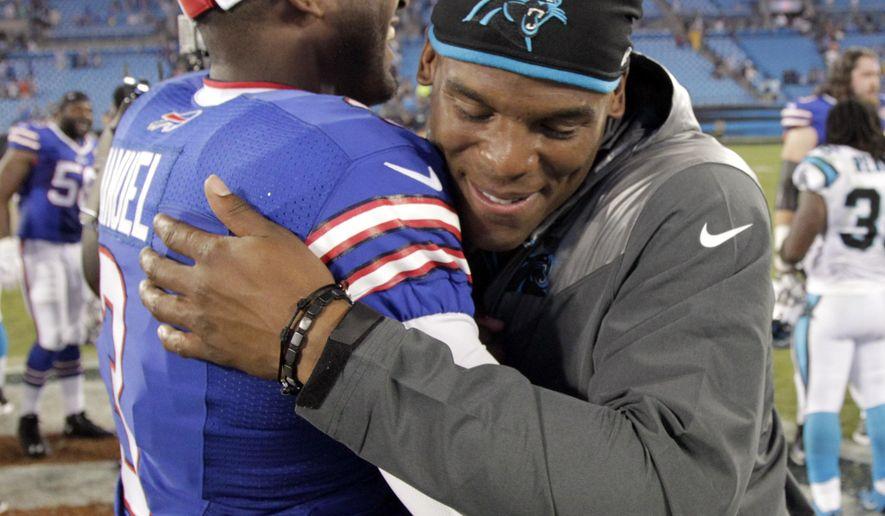 Carolina Panthers' Cam Newton, right, hugs Buffalo Bills' EJ Manuel, left, after a preseason NFL football game in Charlotte, N.C., Friday, Aug. 8, 2014. The Bills won 20-18. (AP Photo/Bob Leverone)