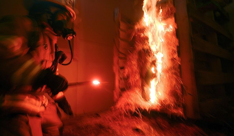 This Aug. 6 2,014 photo shows a firefighter lighting a pile of hay with a flare at the beginning of a Central Emergency Services training drill in Soldotna, Alaska. Crews spent the day in training drills in a new CES facility. (AP Photo/Peninsula Clarion, Rashah McChesney)