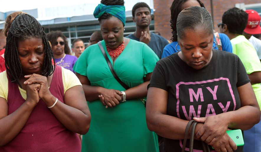 A prayer vigil was held in front of the Ferguson, Mo., police department on Sunday, one day after the shooting. (AP Photo/St. Louis Post-Dispatch, Robert Cohen)