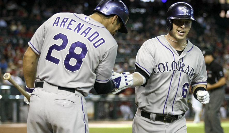 Colorado Rockies' Corey Dickerson (6), right, celebrates with teammate Nolan Arenado (28) after hitting a 10th-inning home run against the Arizona Diamondbacks during a baseball game, Sunday, Aug. 10, 2014, in Phoenix. (AP Photo/Rick Scuteri)