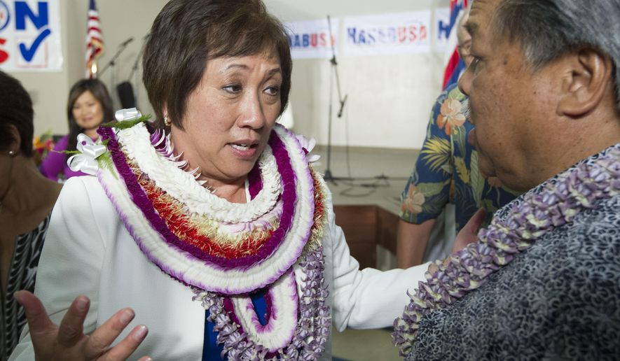 U.S. Rep. Colleen Hanabusa, Democrat, from Hawaii's 1st district, talks to former Hawaii Governor Ben Cayetano, right, at her campaign headquarters Saturday, Aug. 9, 2014, in Honolulu. Hanabusa is locked in a tight race with incumbent Sen. Brian Schatz in the state's Primary Election. (AP Photo/Eugene Tanner)
