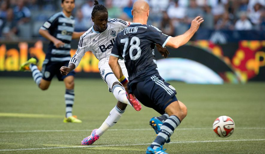 Vancouver Whitecaps' Darren Mattocks, center, of Jamaica, scores a goal as Sporting Kansas City's Aurelien Collin, of France, (78) defends during the first half of an MLS soccer game in Vancouver, British Columbia, on Sunday, Aug. 10, 2014. (AP Photo/The Canadian Press, Darryl Dyck)