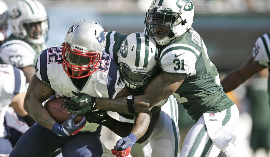FILE - In this Oct. 20, 2013, file photo, New England Patriots' Stevan Ridley (22) is tackled by New York Jets' DeMario Davis, center, and Antonio Cromartie (31) during the second half of an NFL football game in East Rutherford, N.J. Davis, only in his third NFL season, is considered one of the Jets' main leaders despite still being a youngster in the locker room. (AP Photo/Kathy Willens, File)