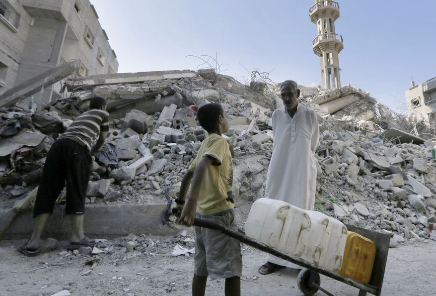 A Palestinian man talks to a boy carrying containers as they stand amid the rubble of al-Qassam mosque, hit by an Israeli airstrike Saturday, in Nusseirat refugee camp in the central Gaza Strip. Egypt has brokered a new 72-hour cease-fire between Israel and Palestine.  (AP Photo/Adel Hana)