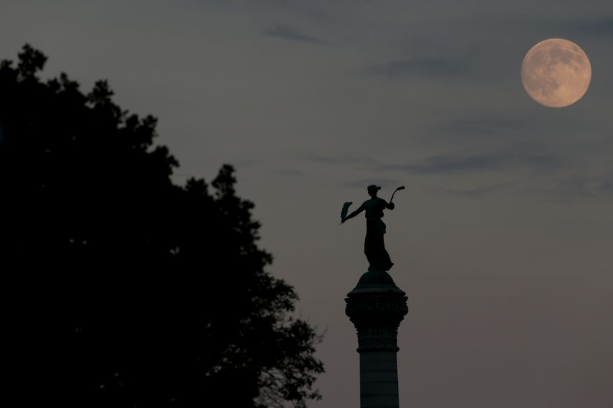 """The moon is seen as it rises over a statue by Harriet A. Ketcham titled """"Victory"""" in the statehouse complex in Des Moines, Iowa, Saturday, Aug. 9, 2014. The moon will reach a full moon stage on Sunday. (AP Photo/Julio Cortez)"""