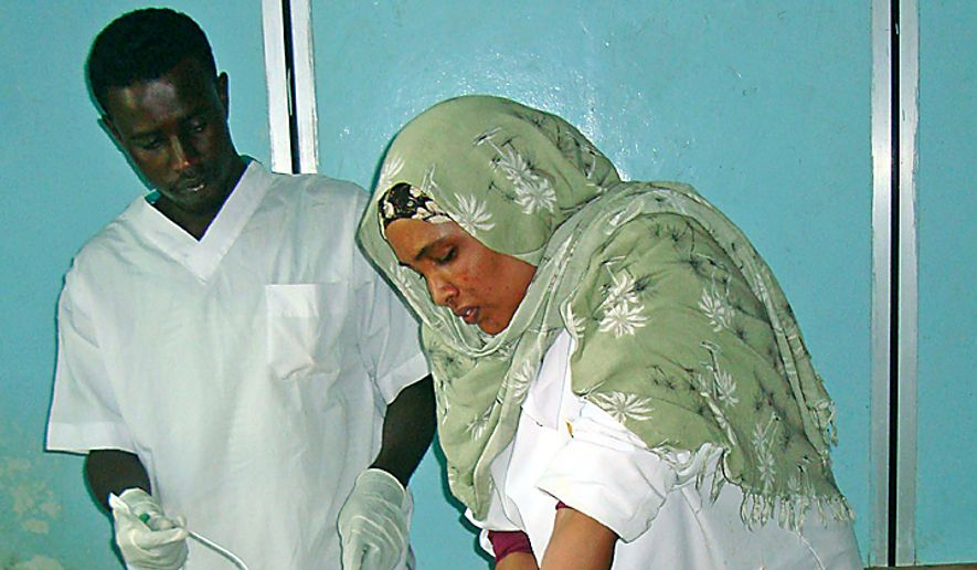Medical personal in Mogadishu's Madina hospital treat a woman wounded by a mortar shell during clashes between Islamist militants and government forces backed by African Union peacekeepers.  (AP Photo/Farah Abdi Warsameh)