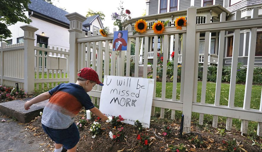 """AJ Polis leaves a flower alongside a placard and a photo of the late actor Robin Williams as Mork from Ork, as people pay their respects at the home where the 80's TV series """"Mork & Mindy"""",was set, in Boulder, Colo., Monday Aug. 11, 2014. Williams, the Academy Award winner and comic supernova whose explosions of pop culture riffs and impressions dazzled audiences for decades and made him a gleamy-eyed laureate for the Information Age, died Monday in an apparent suicide. He was 63. (AP Photo/Brennan Linsley)"""