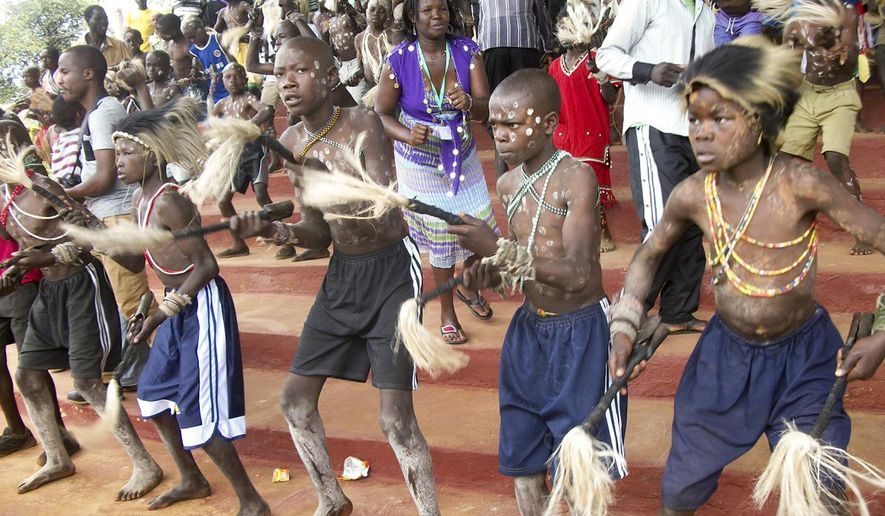 In this photo taken Saturday, Aug. 9, 2014, boys from the Bukusu ethnic group, which prefers traditional circumcision using simple tools and no anesthesia, attend a circumcision ceremony in Bungoma, western Kenya. While the circumcision season among Kenya's Bukusu ethnic group brings a festive atmosphere, at least 12 men from other tribes have been forcibly circumcised since the start of the circumcisions in August 2014, according to police and local authorities, and a group of men from the Turkana tribe wielding swords, bows and clubs held protests last week over the spate of forced procedures. (AP Photo)