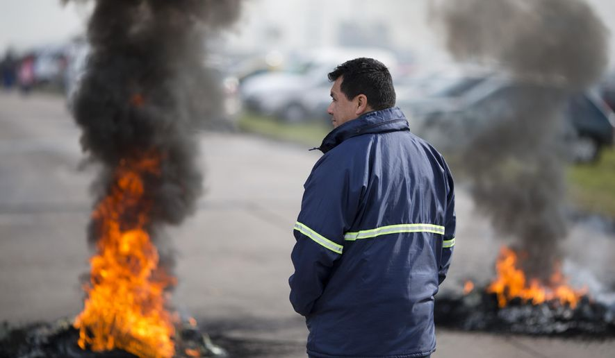 """A worker stands next to burning tires outside the entrance of RR Donnelley printing plant in the outskirts of Buenos Aires, Argentina, Monday, Aug. 11, 2014. RR Donnelley, a Fortune 500 company from Chicago, closed its plant in Argentina without warning catching its 400 workers by surprise when they showed up for work Monday morning. The company posted a letter outside it's entrance announcing its closing due to """"unsolvable crisis."""" (AP Photo/Victor R. Caivano)"""