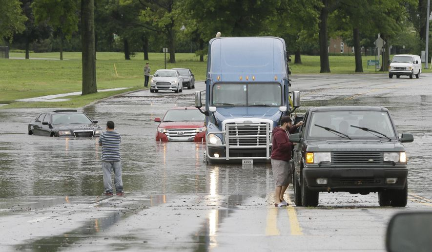 Stranded motorists look over flooded vehicles, Monday, Aug. 11, 2014, in Dearborn, Mich. The Michigan State Police issued an advisory Monday evening, urging drivers to avoid non-essential use of all metro Detroit freeways after heavy rain and thunderstorms left roads flooded and impassable. Interstate 75 at I-94 in Detroit has been shut down in both directions, according to the Michigan Department of Transportation. (AP Photo/Carlos Osorio)
